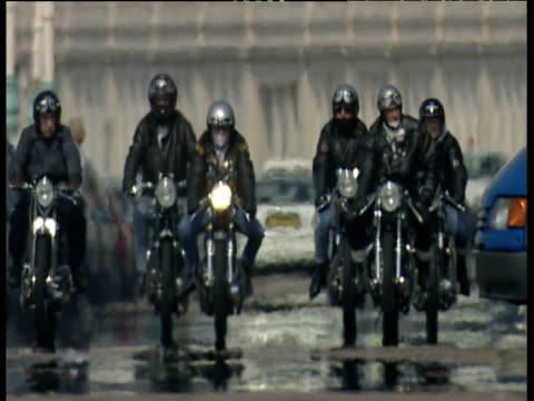 group of bikers wearing jeans helmets and goggles ride towards camera in formation along brighton promenade heat haze causes blurred effect - motorradfahrer stock-videos und b-roll-filmmaterial