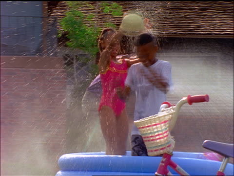 vidéos et rushes de group of black children playing in inflatable pool outdoors as father sprays them with hose - pataugeoire