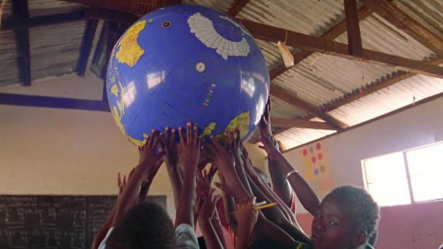 ms group of black schoolchildren holding globe in air / kenya - global village stock videos & royalty-free footage