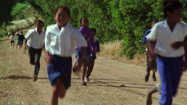 Group of Black schoolchildren running along dirt road / South Africa