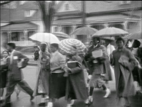 stockvideo's en b-roll-footage met group of black students with umbrellas crossing street / montgomery bus boycott - 1955