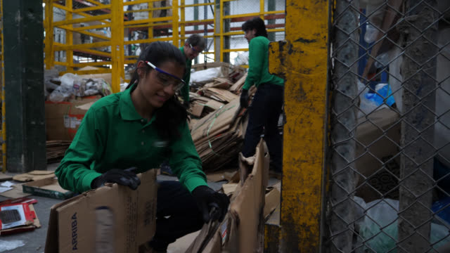 Group of blue collar workers at a recycling factory arranging recycled carton boxes