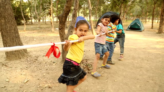 Group of boys and girls playing tug of war, Delhi, India