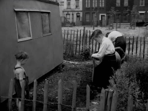 group of boys dig up a vegetable plot in the youth club grounds. 1957. - youth club stock videos & royalty-free footage