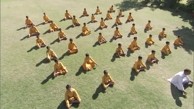 ws cs group of boys in orange robes practicing yoga by following instructor / india - monk stock videos & royalty-free footage