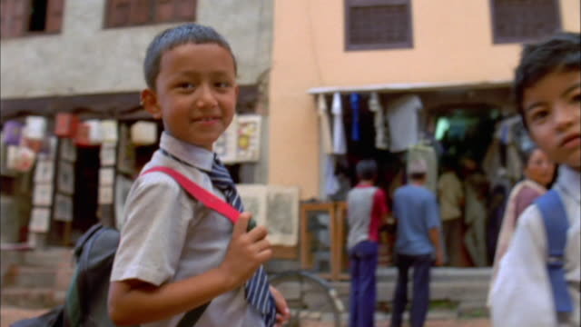 group of boys in school uniform wave and smile at camera available in hd. - nepal stock-videos und b-roll-filmmaterial
