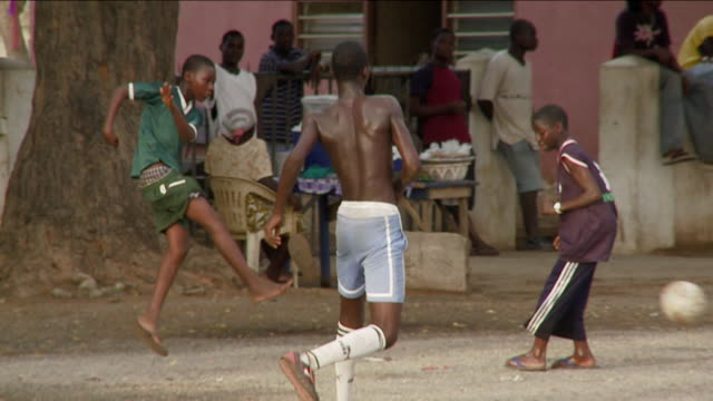 a group of boys kicks a soccer ball around a dirt pitch. available in hd. - ghana stock videos & royalty-free footage
