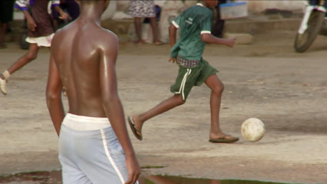 A group of boys kicks a soccer ball around a dirt pitch. Available in HD.