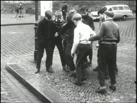 a group of boys look worried after kicking a soccer ball over the berlin wall - 1960 stock-videos und b-roll-filmmaterial