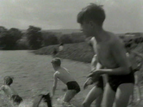 vídeos y material grabado en eventos de stock de a group of boys swim and play in a river near the village of spennithorne 1954 - bañador de hombre