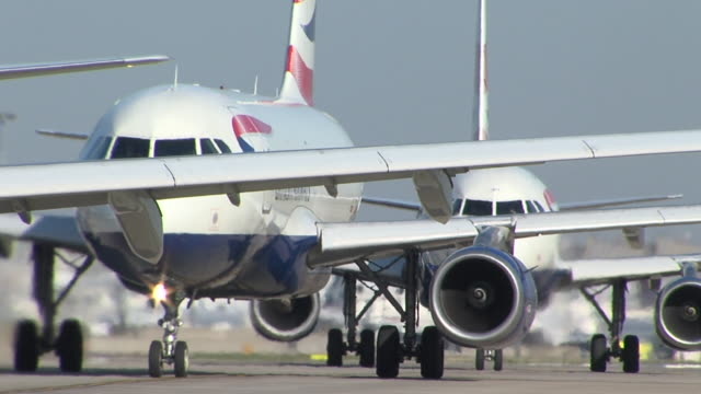 Group of British Airways jets prepare for takeoff at front of Heathrow runway Engines running showing heat haze as they wait for permission to depart