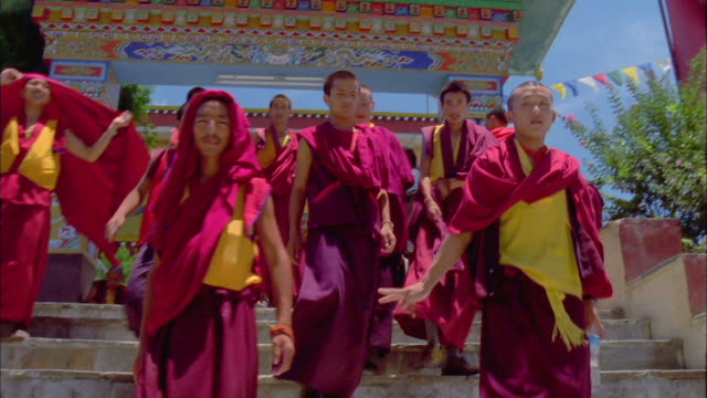 Group of Buddhist monks come out of temple and down steps towards camera, Paro Available in HD.