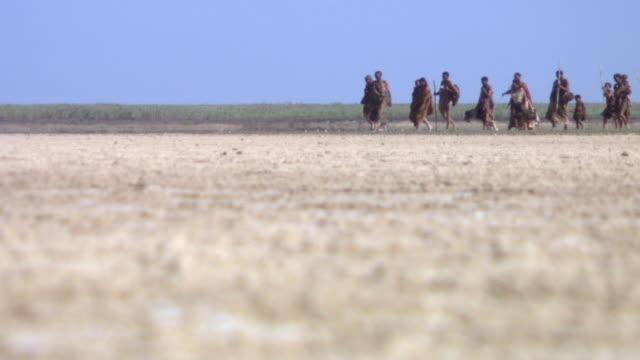 A group of Bushmen hunters walk across a desert landscape. Available in HD.