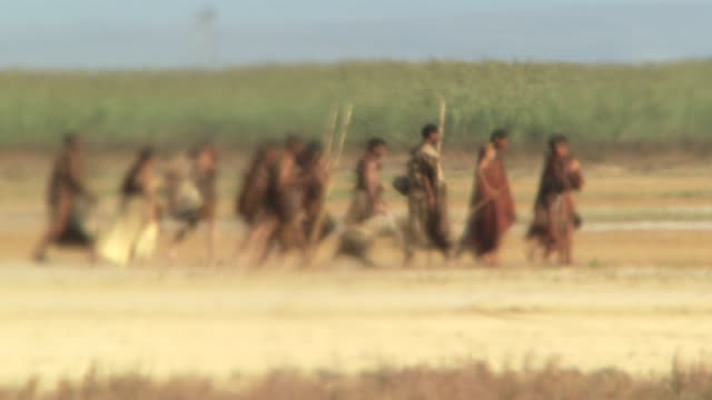 a group of bushmen walk across a desert landscape. available in hd. - arrow bow and arrow stock videos & royalty-free footage