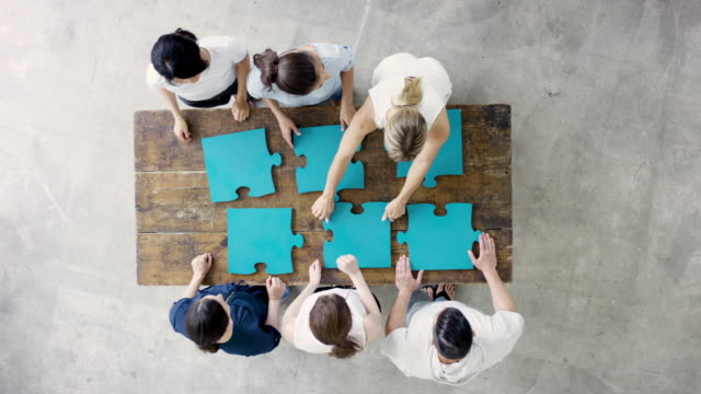 group of business adults sitting around table putting puzzle together - puzzle stock videos & royalty-free footage