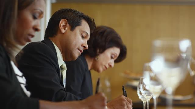MS SELECTIVE FOCUS Group of business associates taking notes, man looking at camera / Bellevue, Washington, USA