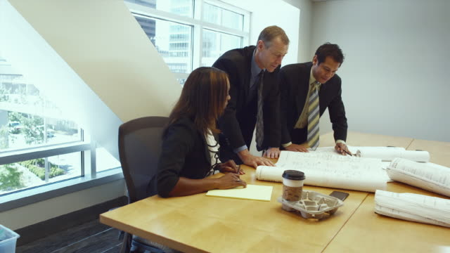 ms group of business associates talking over plans in conference room / bellevue, washington, usa - full suit stock videos and b-roll footage