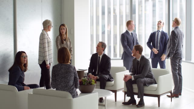 MS Group of business executives in informal discussion in office lobby