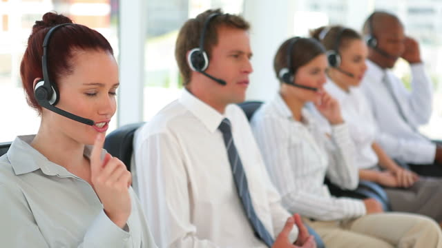 Group of business men and women on headsets
