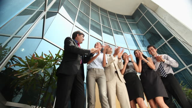 stockvideo's en b-roll-footage met group of business people celebrating success in front of a office building  - compleet pak