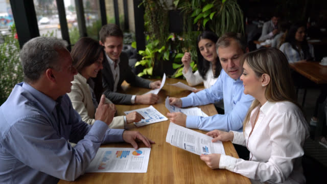 Group of business people discussing something while looking at documents at a restaurant