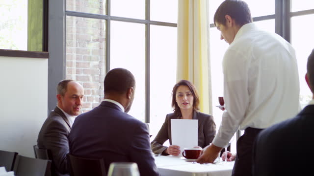 ms group of business people having business meeting at table in restaurant server bringing coffee to table. - offrire un servizio video stock e b–roll