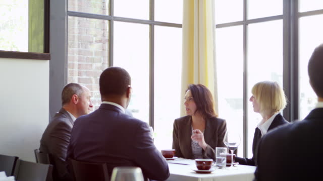 ms group of business people having business meeting at table in restaurant. - formal businesswear stock videos & royalty-free footage