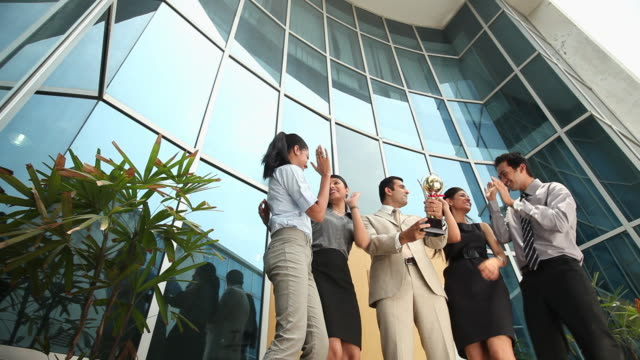 Group of business people holding trophy in front of a office building
