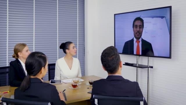 vídeos de stock, filmes e b-roll de grupo de pessoas de negócios olhando para uma tela de projetor com reunião de vídeo-conferência no escritório - teleconferência
