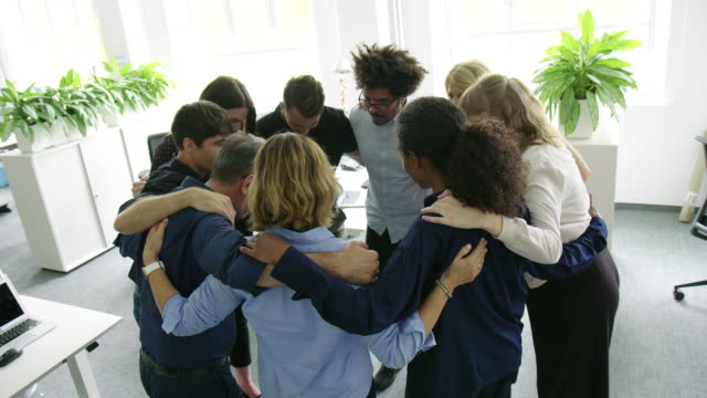 group of business people standing in huddle - arm around stock videos & royalty-free footage