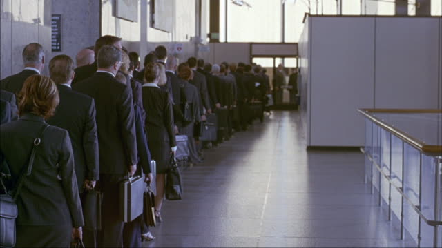 a group of business people wait in a line. - line up stock videos and b-roll footage