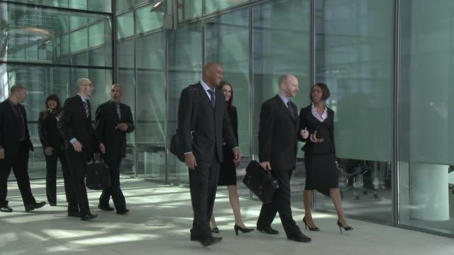ws group of business people walk l to r past camera - 30 34 ��r bildbanksvideor och videomaterial från bakom kulisserna