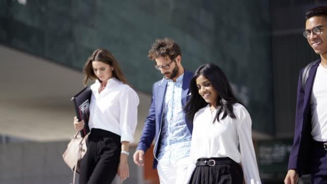vidéos et rushes de groupe de gens d'affaires marcher et de parler dans une ville - quatre personnes
