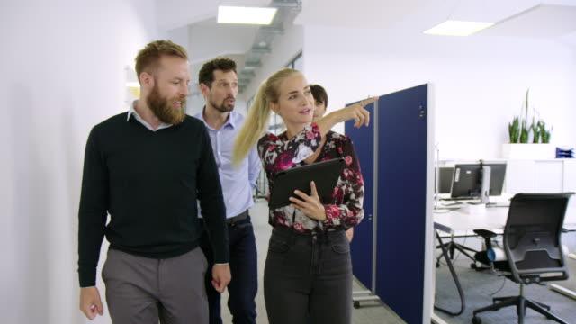 gruppo di uomini d'affari che camminano attraverso il corridoio dell'ufficio - customer video stock e b–roll