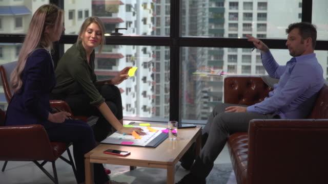 vídeos de stock, filmes e b-roll de grupo de equipe do negócio que arranja a programação na reunião - papel