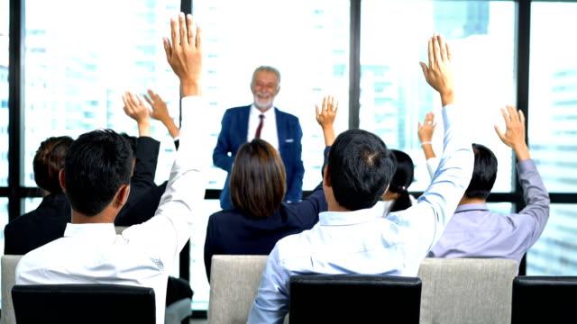 vídeos y material grabado en eventos de stock de grupo de empresarios y mujeres de negocios que se levantan para hacer preguntas al orador masculino en la sala de conferencias en el evento de conferencia. audiencia levantando de la mano durante el seminario. - preguntar