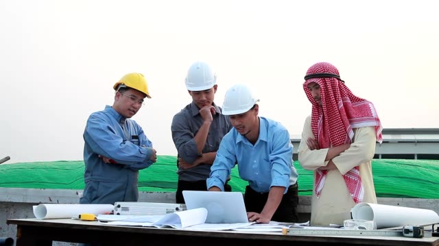 group of businessmen and engineers of diverse ethnic backgrounds meeting discuss and clarify something about working on the construction site to the team. - explaining stock videos & royalty-free footage