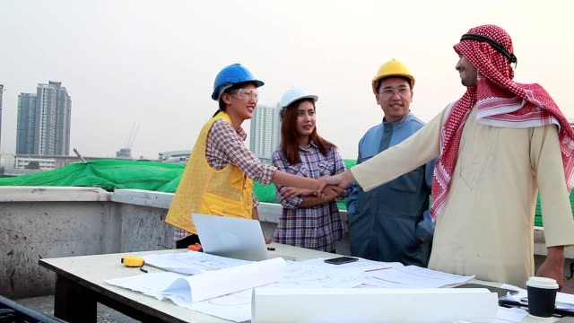 group of businessmen and engineers of diverse ethnic backgrounds meeting discuss and clarify something about working on the construction site to the team. - financial occupation stock videos & royalty-free footage