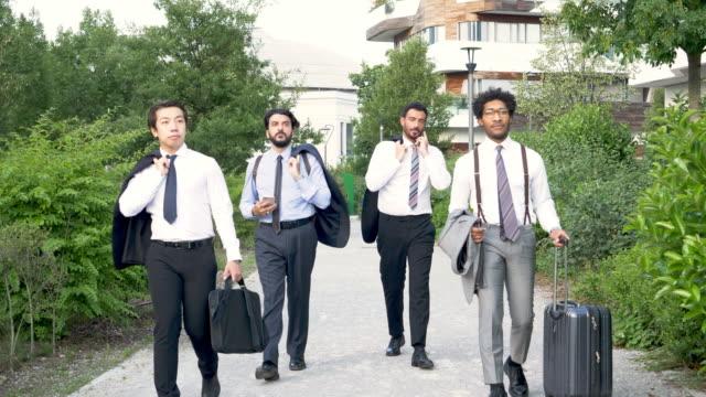 vídeos de stock, filmes e b-roll de group of businessmen walking on footpath - camisa e gravata