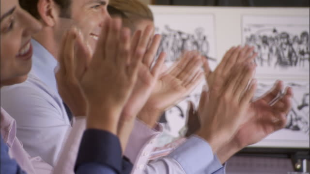 CU, SELECTIVE FOCUS, Group of businesspeople clapping in conference room, Los Angeles, California, USA
