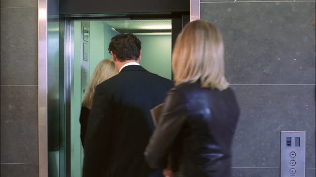 a group of businesspeople get onto an elevator. - arbeitskollege stock-videos und b-roll-filmmaterial