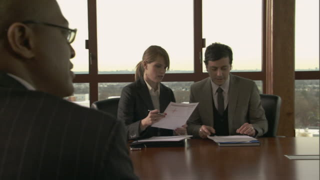 vídeos de stock e filmes b-roll de ms group of businesspeople in conference room/ pan woman arriving, showing man a document, and sitting down/ montclair, new jersey - sentar se