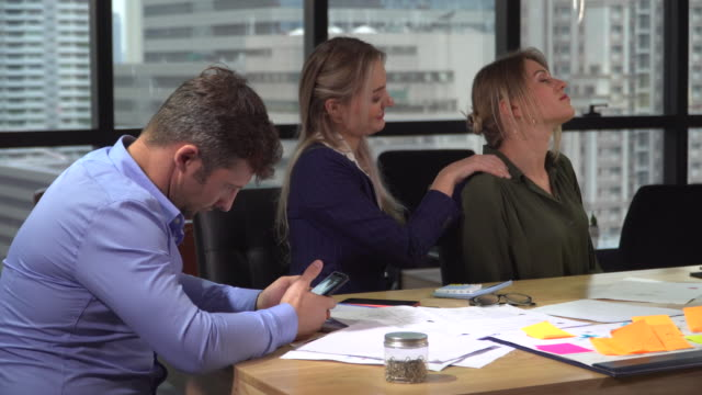 vídeos de stock e filmes b-roll de group of businesspeople relaxing in the office - dor no pescoço