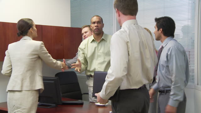 Group of businesspeople shaking hands and leaving office