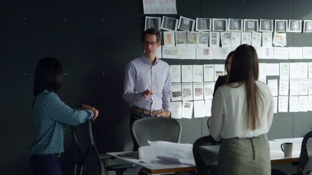 MS Group of businesspeople standing at conference table in office having informal meeting