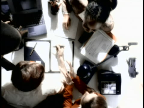 overexposed overhead pan group of businesspeople talking + working around cluttered desk - overexposed stock videos & royalty-free footage