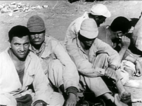 vídeos de stock e filmes b-roll de group of captured egyptian soldiers sitting on ground / suez crisis / middle east - 1956