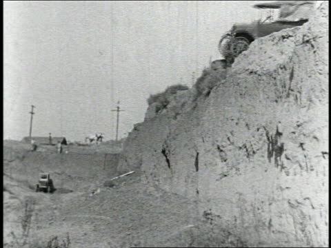 b/w 1925 group of cars falling off hill into pit as men run to them / feature - anno 1925 video stock e b–roll