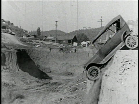 vidéos et rushes de b/w 1925 group of cars falling off hill into pit / feature - cliff
