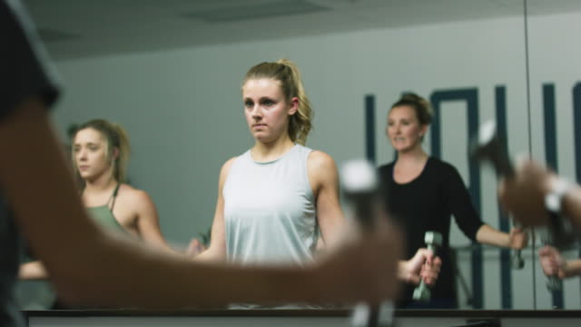 A Group of Caucasian Women in Their Twenties Perform Arm Exercises in a Class in an Exercise Studio